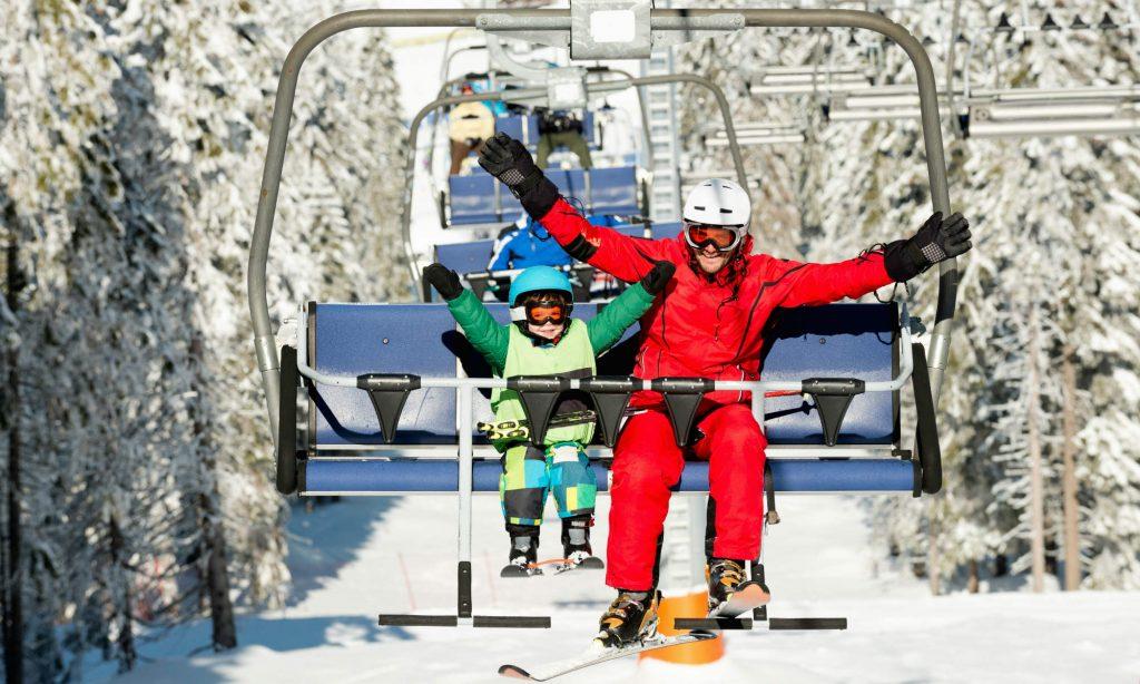 Wie Kinder Skifahren lernen: Ein kleines Kind und sein Skilehrer fahren mit dem Lift.