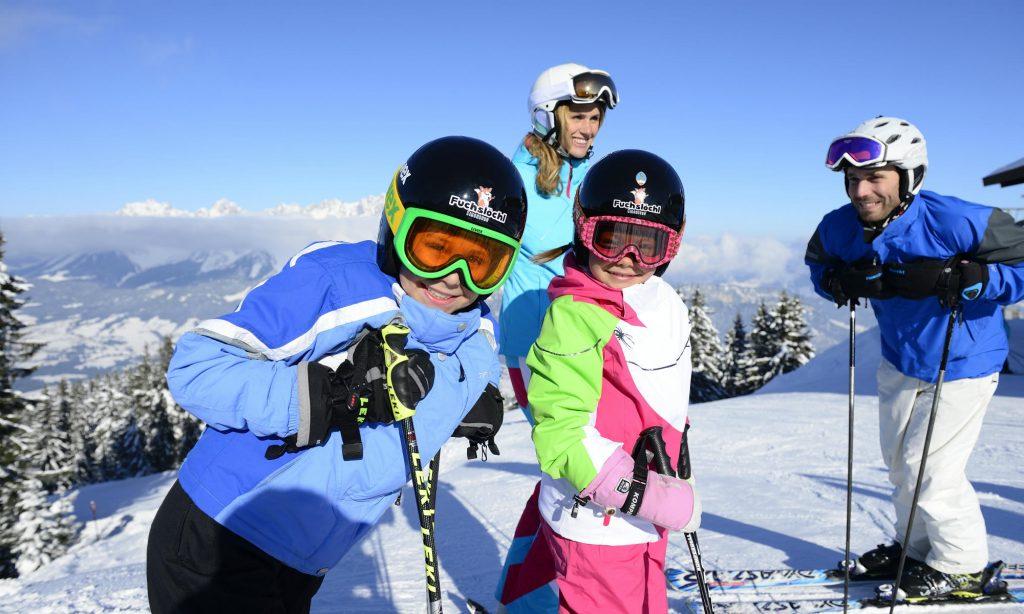 Eltern mit ihren Kindern beim Skifahren lernen.