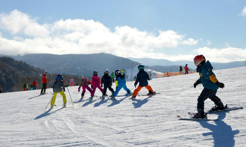 Eine Gruppe Kinder beim Skifahren lernen auf der Piste.
