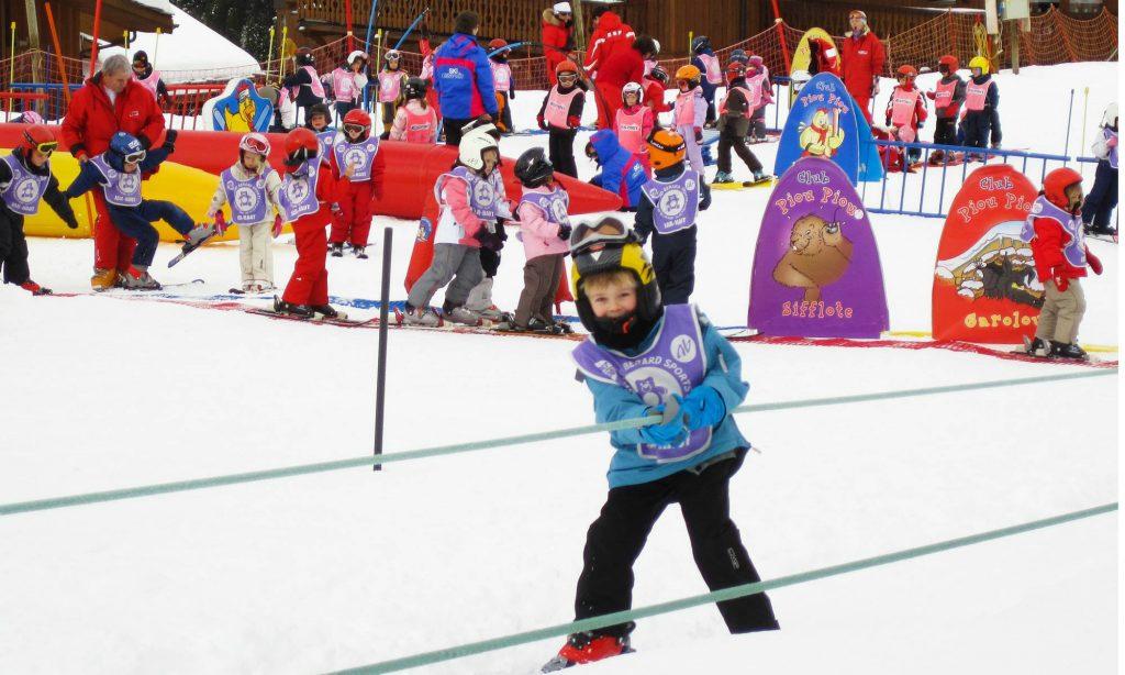 In einem bunten Übungsgelände haben Kinder Spaß beim Skifahren lernen